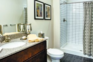 Shower and toilet in a bathroom inside The Yards at Fieldside Village apartments.