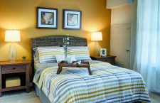 A bed with a breakfast table in a bedroom at The Yards at Fieldside Village apartments.