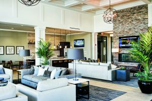 Couches and fireplace in the seating area of the lobby at The Yards at Fieldside Village apartment community.