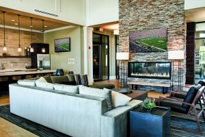 A couch and fireplace in the seating area of the lobby at The Yards at Fieldside Village apartment community.